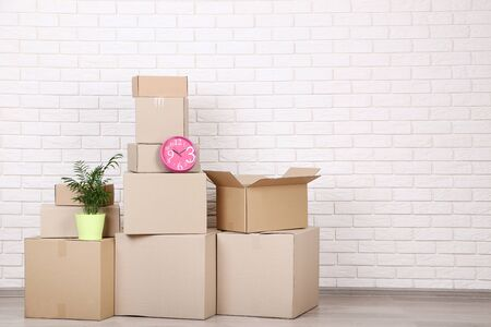 Cardboard boxes with household stuff on brick wall background 版權商用圖片