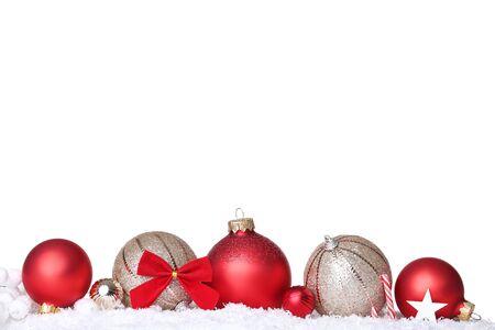 Bolas de Navidad con nieve y dulces sobre fondo blanco.