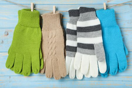 Knitted mittens hanging on blue wooden background