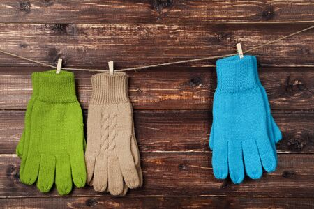 Knitted mittens hanging on brown wooden background