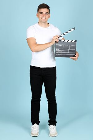 Young man with black clapper board on blue background