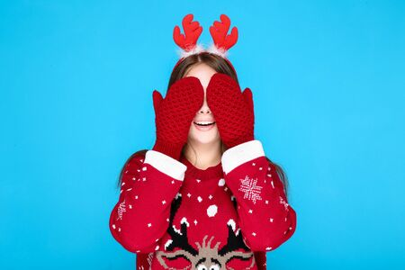 Beautiful woman in christmas sweater, gloves and red horns on blue background