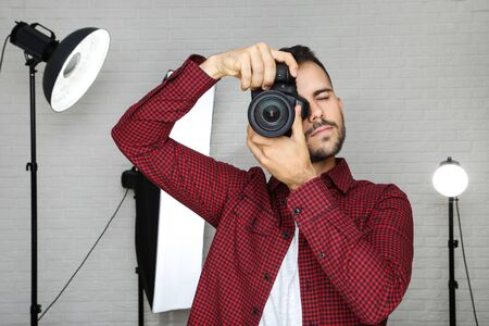 Young photographer with camera and professional studio equipment on grey background