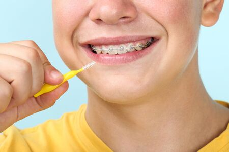 Young man with toothbrush on blue background