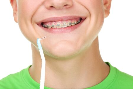 Young man with toothbrush on white background
