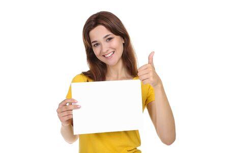 Mujer joven con hoja de papel en blanco y pulgar hacia arriba sobre fondo blanco. Foto de archivo