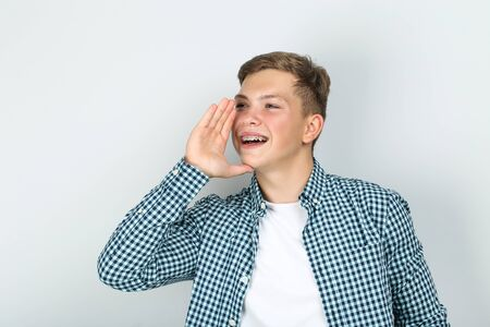 Jeune homme avec des appareils dentaires criant sur fond gris