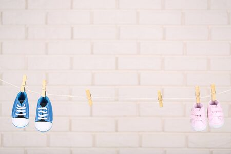 Baby shoes hanging on brick wall background