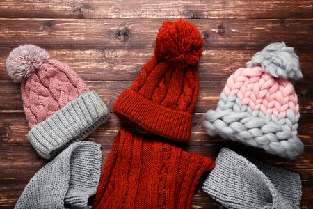 Knitted hats and scarfs on brown wooden table Banque d'images