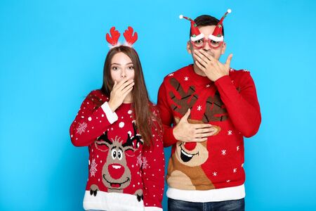 Beautiful man and woman wearing christmas sweaters with red horns and eyeglasses on blue background