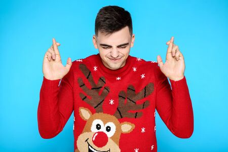 Beautiful man in red christmas sweater on blue background 版權商用圖片