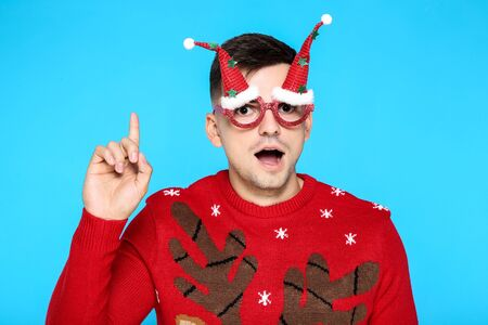 Beautiful man in christmas sweater and eyeglasses on blue background