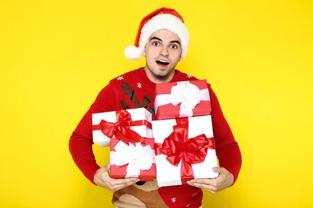 Beautiful man wearing christmas sweater, santa hat and holding gift box on yellow background