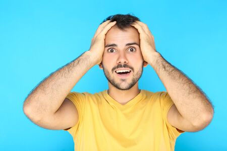 Portrait of young surprised man on blue background Stock Photo