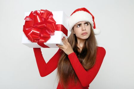 Beautiful woman wearing santa hat and holding gift box on grey background