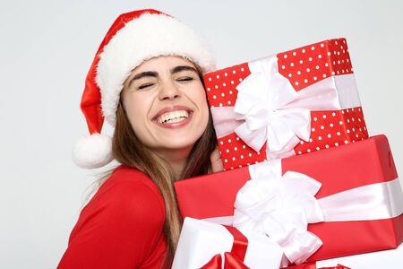 Beautiful woman wearing santa hat and holding gift boxes on grey background 版權商用圖片