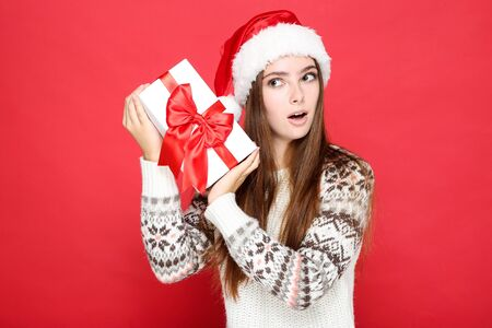 Beautiful woman wearing sweater, santa hat and holding gift box on red background 版權商用圖片