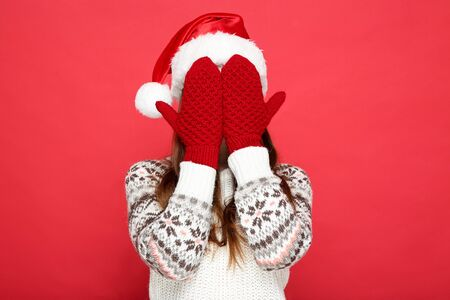 Beautiful woman wearing sweater, gloves and santa hat on red background 版權商用圖片