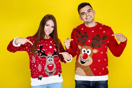 Beautiful man and woman in christmas sweaters on yellow background