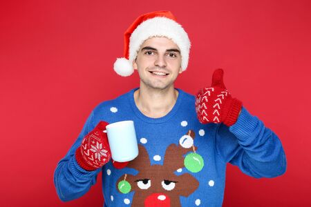 Beautiful man wearing christmas sweater, santa hat, gloves and holding cup of tea on red background