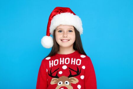 Little girl in christmas sweater and hat on blue background