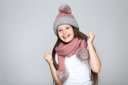 Little girl in hat and scarf on grey background