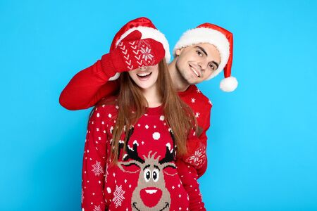 Beautiful man closing woman eyes in christmas sweater and santa hats on blue background 版權商用圖片