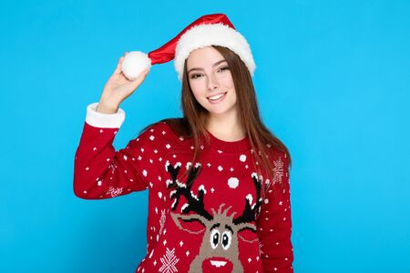Beautiful woman in christmas sweater and santa hat on blue background