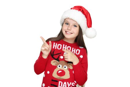 Little girl in christmas sweater and hat pointing by fingers on white background 版權商用圖片