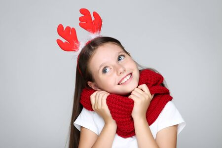 Little girl in christmas red horns and knitted scarf on grey background