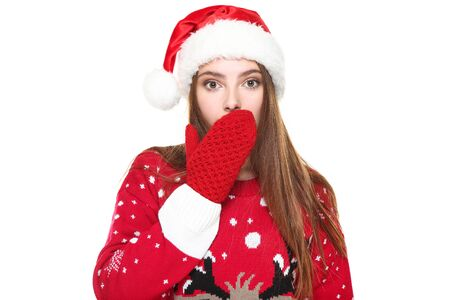 Beautiful woman wearing christmas sweater, gloves and santa hat on white background