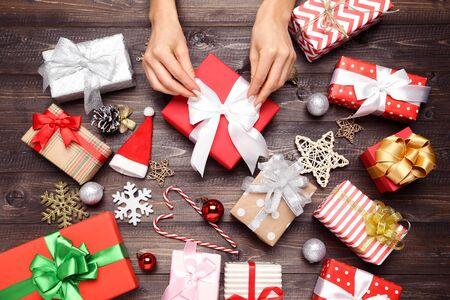 Confezione regalo in mani femminili con ornamenti natalizi su fondo in legno