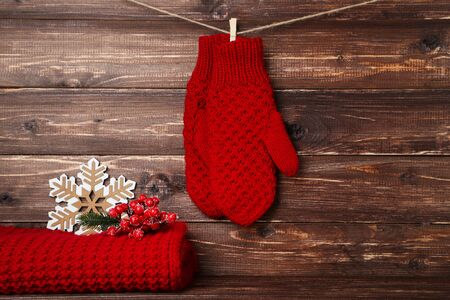 Knitted mittens with scarf, red berry and snowflake on brown wooden background Foto de archivo