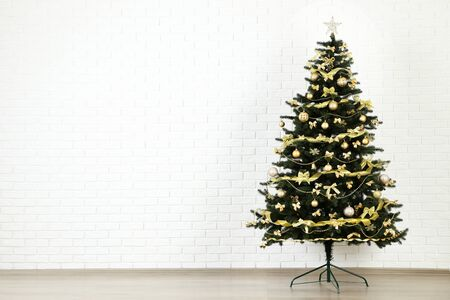 Christmas fir tree with ornaments on white brick wall background