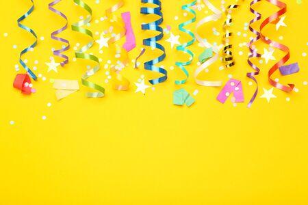 Rubans colorés avec des étoiles en papier et des confettis sur fond jaune