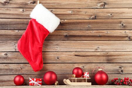 Red christmas stocking with wooden sleigh and baubles on brown background