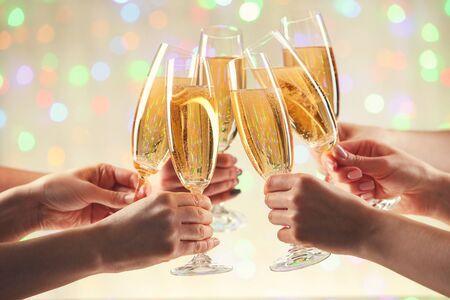 Female hands clink glasses of champagne on blurred lights background