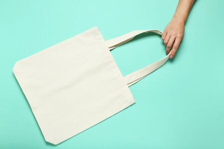 Female hand holding white cotton eco bag on mint background