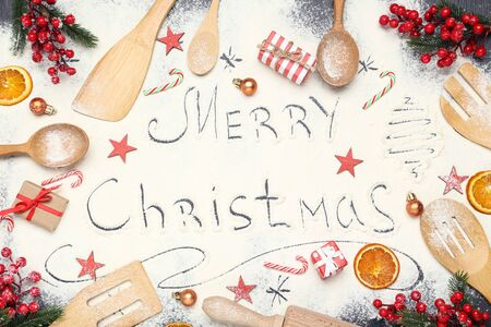 Text Merry Christmas on flour with kitchen utensils and ornaments