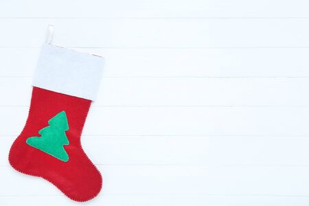 Red christmas stocking on white wooden table