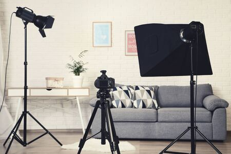 Photo studio with professional equipment and home interior on brick wall background