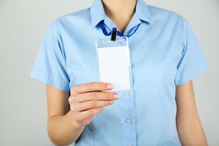 Female hand showing blank white bagde on grey background Foto de archivo