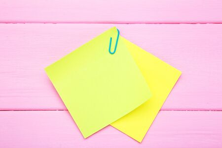 Paper sticky notes on pink wooden table