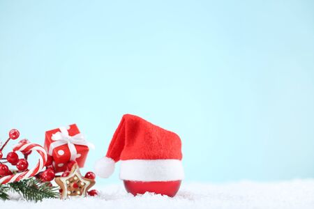 Red santa hat with bauble, gift box and candy on blue background Stock Photo