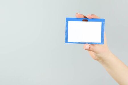 Female hand holding blank white bagde on grey background
