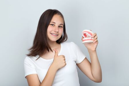 Young girl with dental braces holding teeth model and showing thumb up on grey background