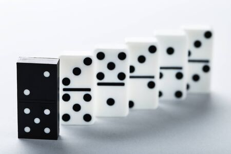 Leader concept. Domino tiles on grey background