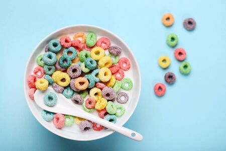 Colorful corn rings in bowl with milk and spoon on blue background