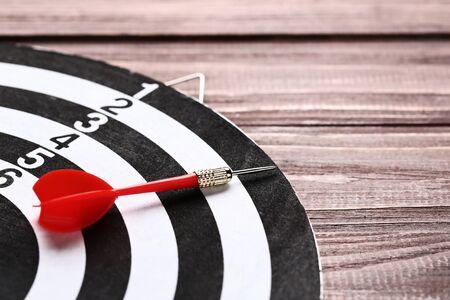 Dartboard with darts on brown wooden table 版權商用圖片
