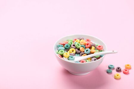 Colorful corn rings in bowl with milk and spoon on pink background